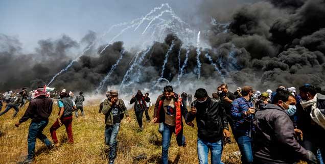 Während Palästinenser Autoreifen anzünden, die die Luft mit Rauch füllen, schießt Israel mitTränengas auf die Demonstranten. Die Proteste spielen sich allesamt auf palästinensischem Territorium im Gazastreifen ab. (Foto: Mohammed Talatene/dpa)
