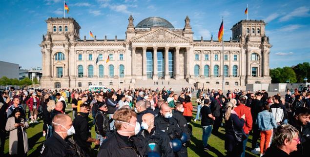 Polizeibeamte mit Mund-Nasen-Schutz in einer Menschenmenge vor dem Reichstagsgebäude. (Foto: pa/Nietfeld)