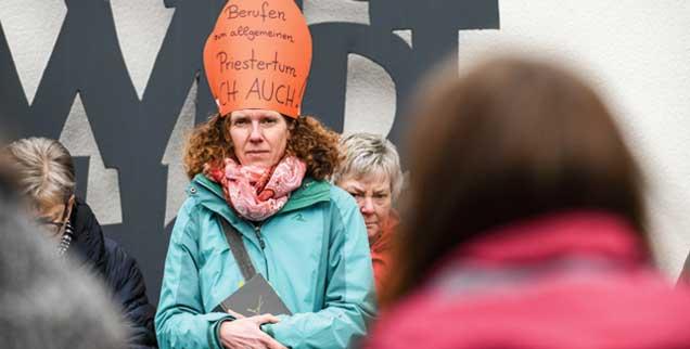 """""""Berufen zum allgemeinen Priestertum ICH AUCH!"""", steht auf der Mitra, die eine Frau aus Protest aufgesetzt hat. Katholikinnen und Katholiken demonstrieren am Rande der Bischofskonferenz in Lingen für die Gleichberechtigung von Frauen in der katholischen Kirche (Foto: KNA)"""