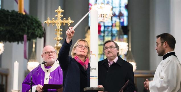Mal sehen, ob es brennt. Karin Kortmann, Vizepräsidentin des Zentralkomitees der Katholiken in Deutschland zündet im Münchner Dom die Synodalkerze an. Links: Kardinal Marx (Foto: epd/Balk)