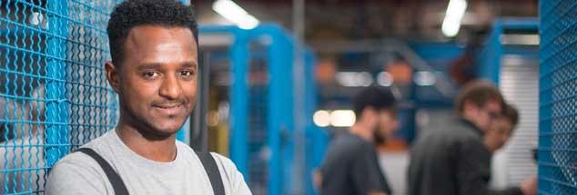 Tedros Gebru an seinem Arbeitsplatz beim Kabelhersteller Lapp in Stuttgart: Nach seiner Flucht aus Eritrea hat er im Betrieb eine Ausbildung abgeschlossen und arbeitet nun in der Kabelherstellung. Künftig könnten Wege nach Deutschland auch über ein Einwanderungsgesetz führen, das die Regierungskoalition entworfen hat. (Foto: pa/Gollnow)