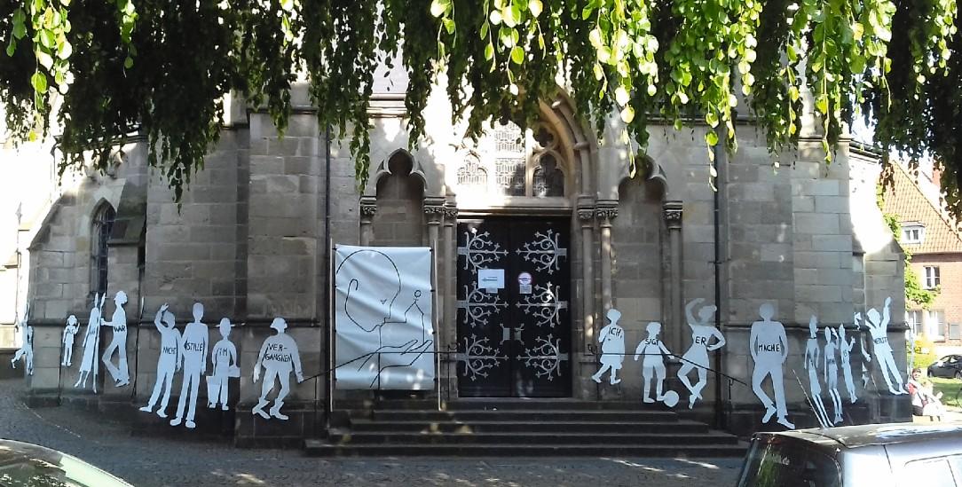 Tanzende Pappfiguren an der Heilig-Kreuz-Kirche in Münster: Das Kunstprojekt von Maria 2.0 entstand an einem Samstag im Mai – und wurde nur Stunden später geschändet (Foto: Kötter)