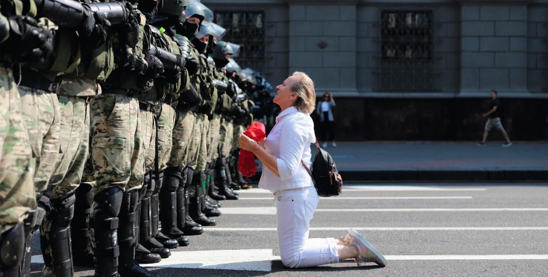 Innere Stärke: Allein und auf Knien protestiert diese Frau in Minsk gegen martialisch ausgestattete Polizisten (Foto: pa/ap)