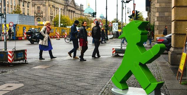 Nicht überall ist so viel Platz: Fußgänger und grünes Ampelmännchen auf einem Bürgersteig in Berlin (Foto: iStock by Getty/Avunchik)
