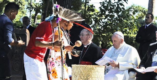 Politische Anklagen, beeindruckende Hearings, konservative Empörung, indigene Ritenund ein neuer Katakombenpakt. Beobachtungen aus RomEin Kanu für den Vatikan: Indigene tragen ein Boot in die Aula der Amazonassynode. (pa/ap/Alessandra Tarantino)