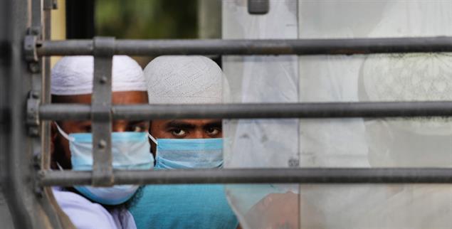 Neu-Delhi: Muslimische Pilger warten auf einen Bus, der sie in eine Quarantäne-Station bringen soll (Foto: pa/Swarup)