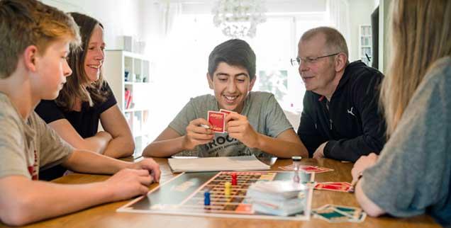 Gesellschaftspiel mit Familienanschluss: Abdulkarim (Mitte) aus Syrien lebt in Bremen bei Pflegefamilie Wilken. Er ist einer von Tausenden unbegleiteten minderjährigen Flüchtlingen in Deutschland. (Foto: epd/ Michalak)