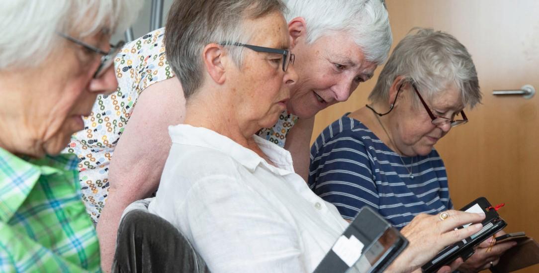 Digitales Einmaleins: Dagmar Hirche (stehend) zeigt ihren Kursteilnehmerinnen, was ihr Smartphone alles kann (Foto: Desmarowitz))