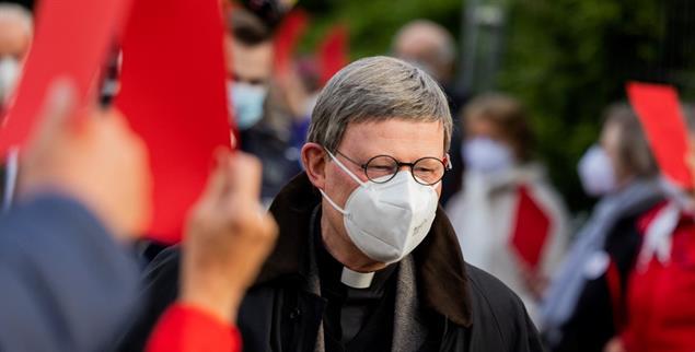 Rote Karten für den Kardinal: Mitglieder der Gemeinde St. Maria vom Frieden protestieren gegen Kölns Erzbischof Rainer Maria Woelki (Foto: dpa)