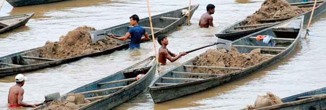 Der Abbau ist in Indien harte Arbeit: Männer stehen bis zum Bauch im Wasser und schaufeln aus dem Kulsi-Fluss Sand in ihre Boote (Foto: pa/epa)