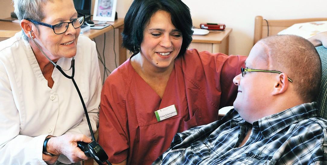 Zuwendung und Linderung statt Sterbehilfe: In einem Hospiz sprechen eine Palliativmedizinerin und eine Palliativ-Krankenschwester mit einem Patienten (Foto: pa/Grubitzsch)