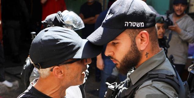 Protest in Jerusalem: Ein Demonstrant und ein israelischer Sicherheitsbeamter stehen sich gegenüber (Foto: REUTERS/Ammar Awad)