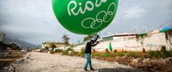 Hier steht heute ein Olympia-Stadion: Ein Arbeiter hält im August 2014 einen grünen Ballon mit der Aufschrift »Rio 2016« hoch. Im August 2016 sieht es an dieser Stelle ganz anders aus. (Foto: pa/dpa/Michael Kappeler)