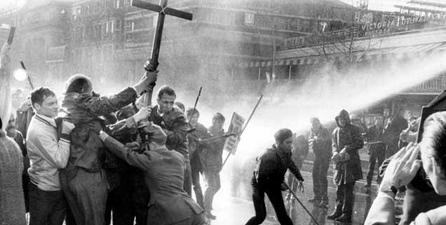 14. April 1968, Berlin, Demonstranten mit Kreuzen im Strahl der Wasserwerfer: Nach dem Anschlag auf Rudi Dutschke halten die öffentlichen Proteste an. Bei dieser Demo am Ostersonntag sind es über 2500 Ostermarschierer und Angehörige der außerparlamentarischen Opposition, die mehr Demokratie und einen grundlegenden Wandel der Gesellschaft  fordern. (Foto: pa/Giehr)