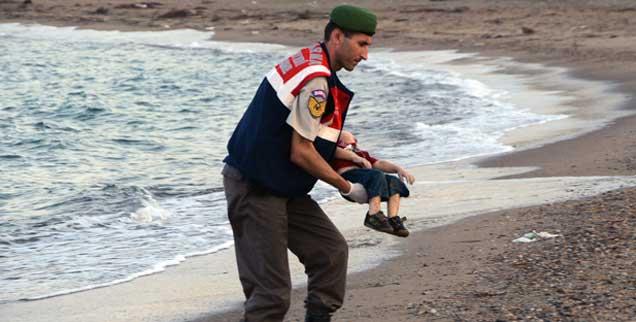 Dieses Foto geht um die Welt: Ein kleiner Junge ist tot. Gestorben im Meer, auf der Flucht aus Syrien. Seine Leiche wird von einem Helfer geborgen. (Foto: pa/ap)