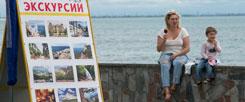 Einsames Eisschlecken in Jewpatorija auf der Krim: Seit der Annexion der Halbinsel durch Russland kommen kaum noch Touristen. Da hilft alle Werbung für attraktive Ausflugsziele (links) nichts. (Foto: pa/dpa/sputnik/Sergey Malgavko)