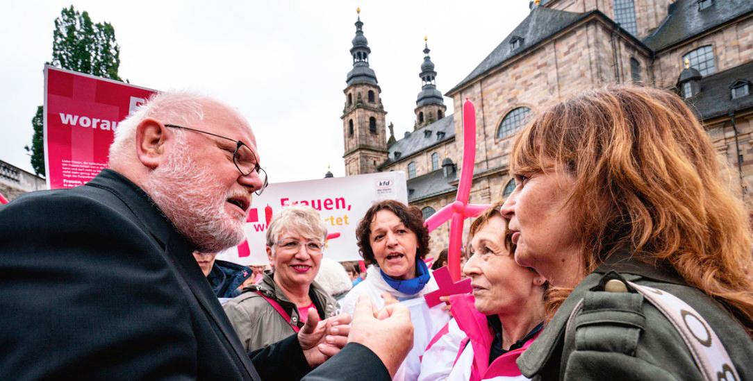 Verstehst Du, was ich meine? Kardinal Marx diskutiert mit einer Demonstrantin vor dem Dom (Foto: pa/Rumpenhorst)