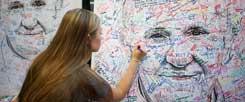 Franziskus als Projektionsfläche: Eine Studentin aus Minnesota unterschreibt auf einem Papstposter für Reformwünsche. (Foto: Reuters/Mark Makela)
